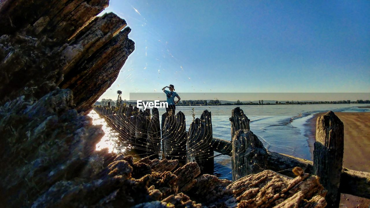 rock - object, nature, outdoors, beauty in nature, sunlight, scenics, real people, tranquility, day, clear sky, sky, sea, water