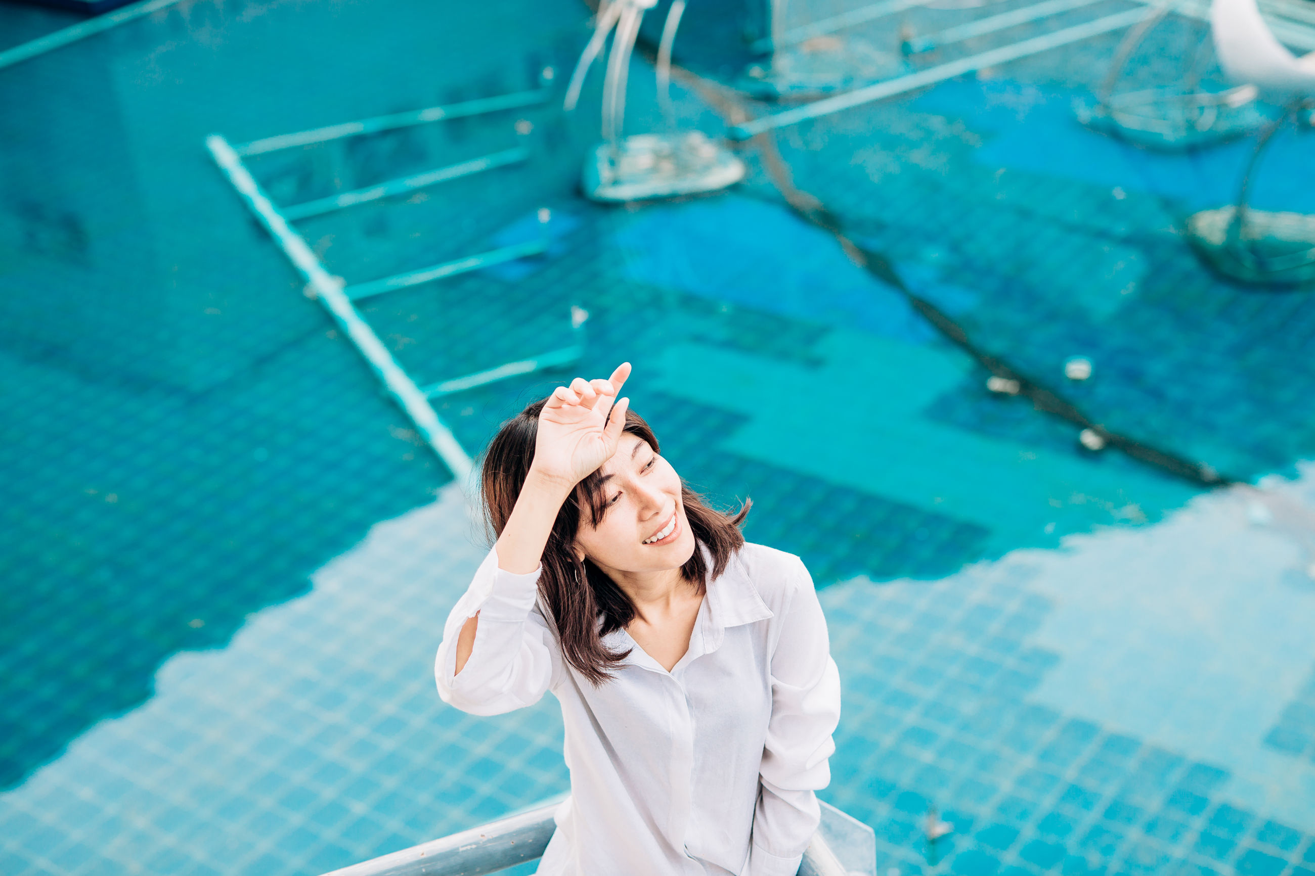 High angle view of woman sitting at swimming pool