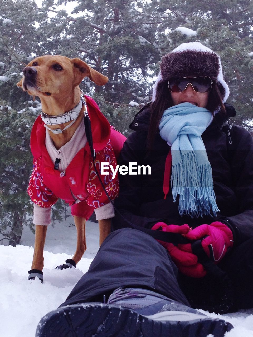 Woman sitting with dog on snowy field