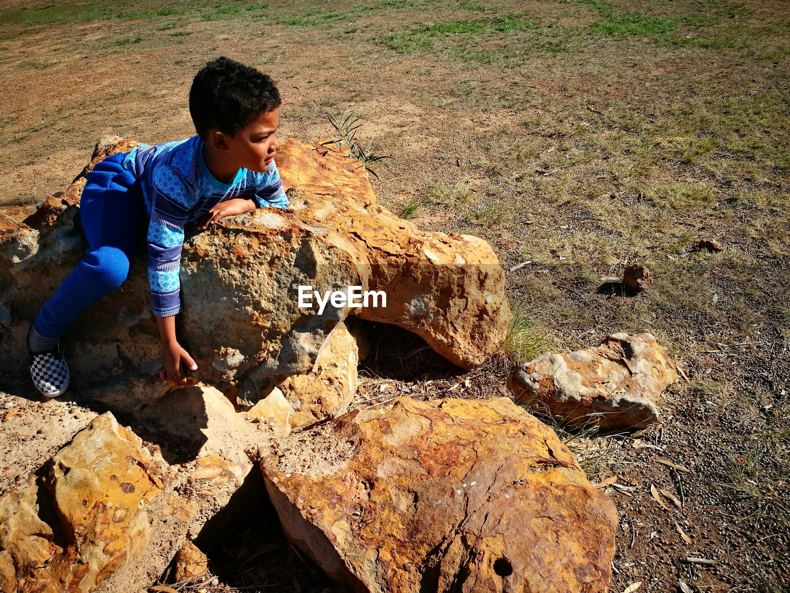 High angle view of boy sitting on rocks at field