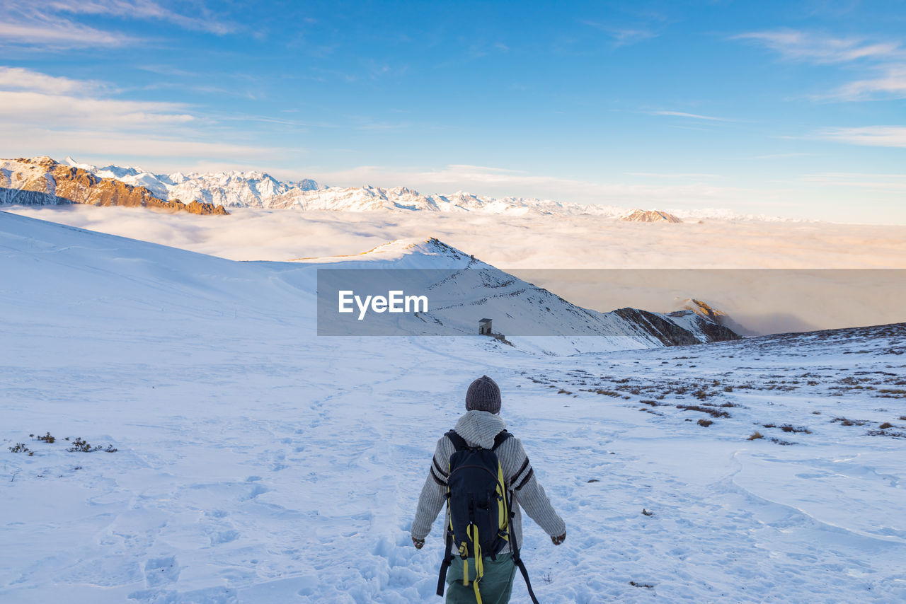 Rear View Of Woman With Backpack On Snow Covered Landscape