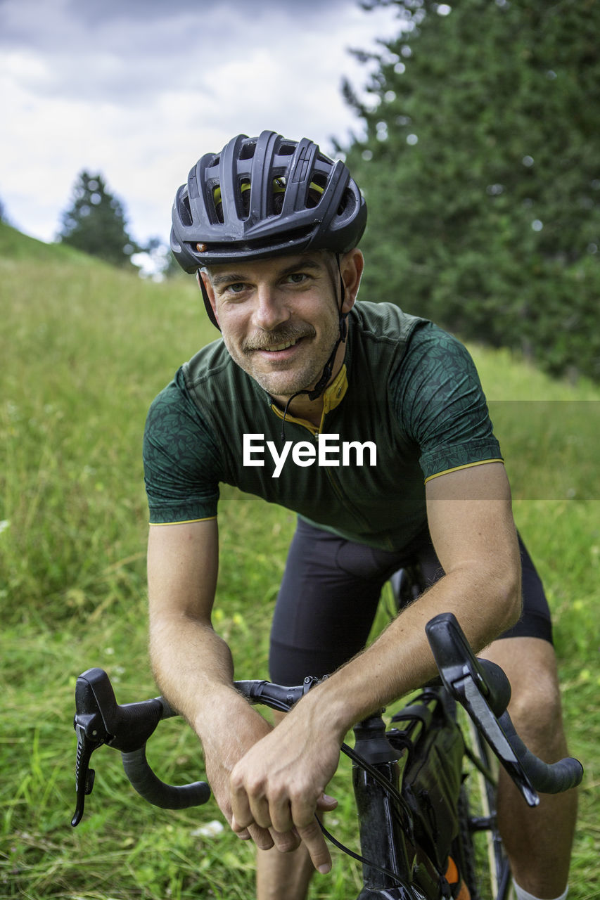Portrait of man riding bicycle outdoors
