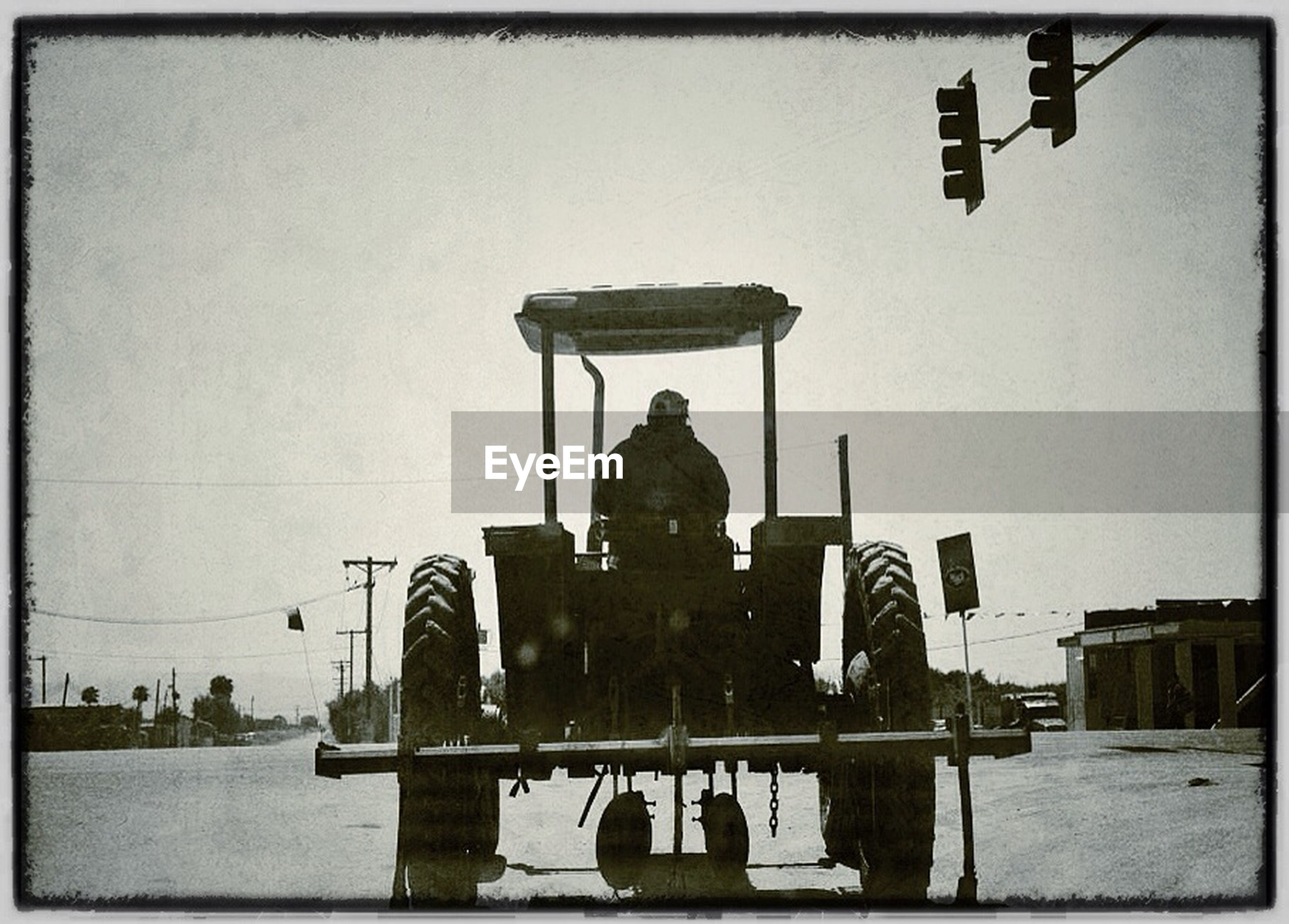 Rear view of man sitting on tractor against sky