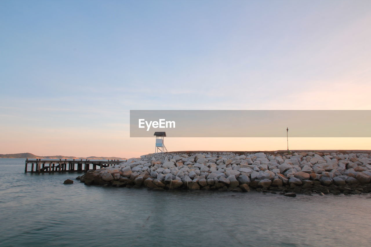 water, sky, sunset, sea, scenics - nature, built structure, architecture, waterfront, beauty in nature, nature, no people, solid, tranquil scene, rock, building exterior, tranquility, cloud - sky, tower, groyne, horizon over water, outdoors, wooden post