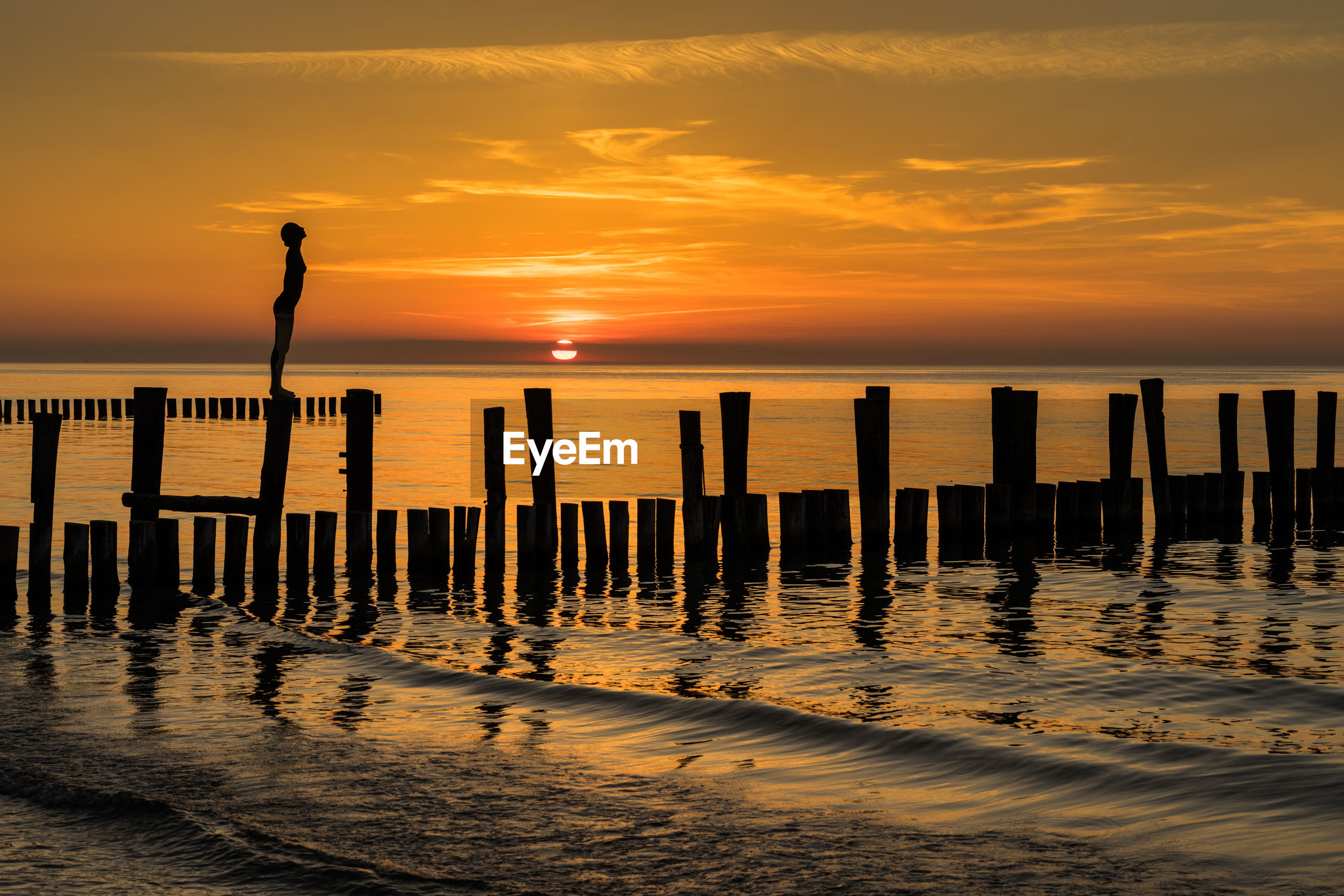 Silhouette woman standing on wooden post at beach against sky during sunset