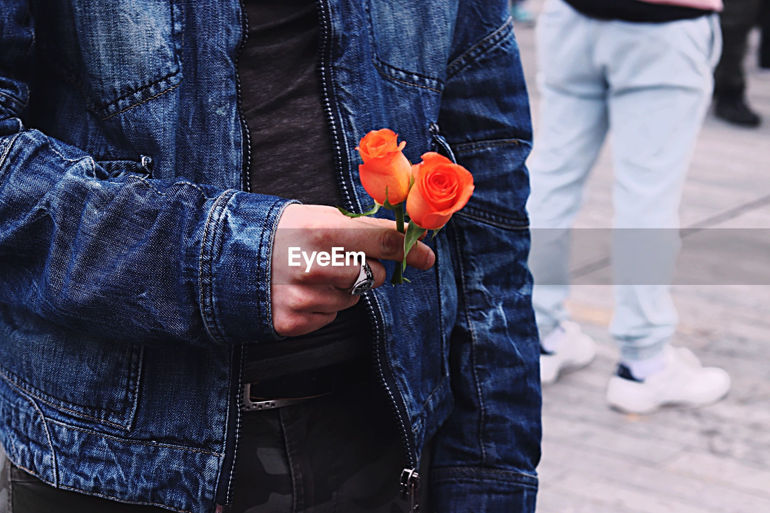 Close-up midsection of man holding roses on street