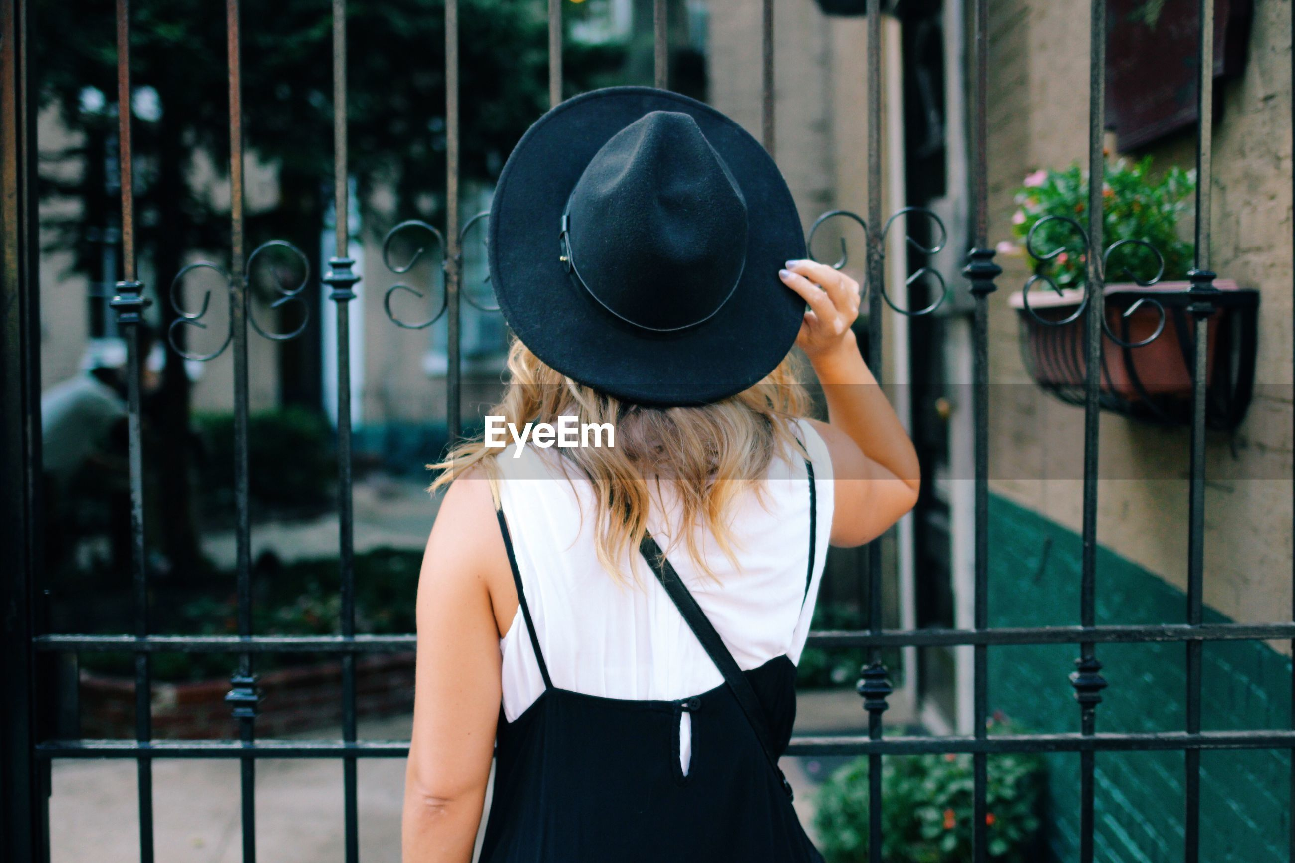 Rear view of woman with hat by iron fence