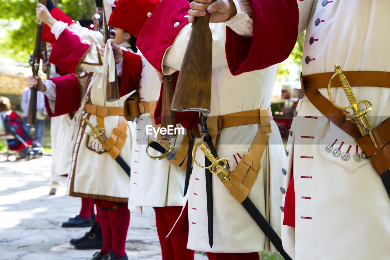 Midsection of men wearing traditional costumes while holding guns on footpath