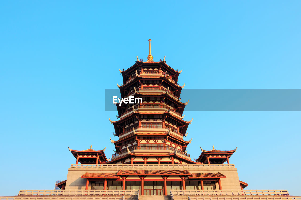 Low angle view of traditional building against clear blue sky on sunny day