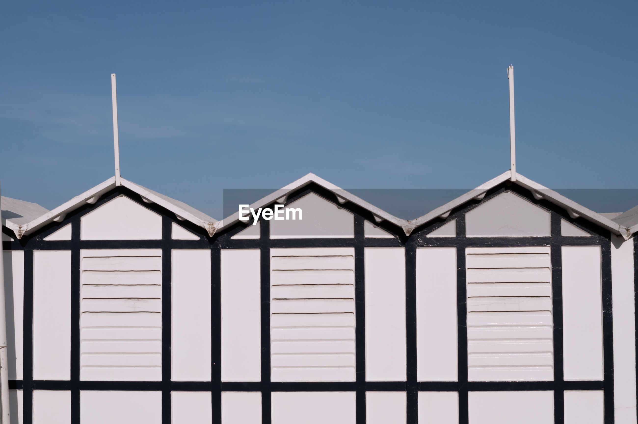 Detail of typical beach huts in italy. white, with a beautiful blue sky in the background