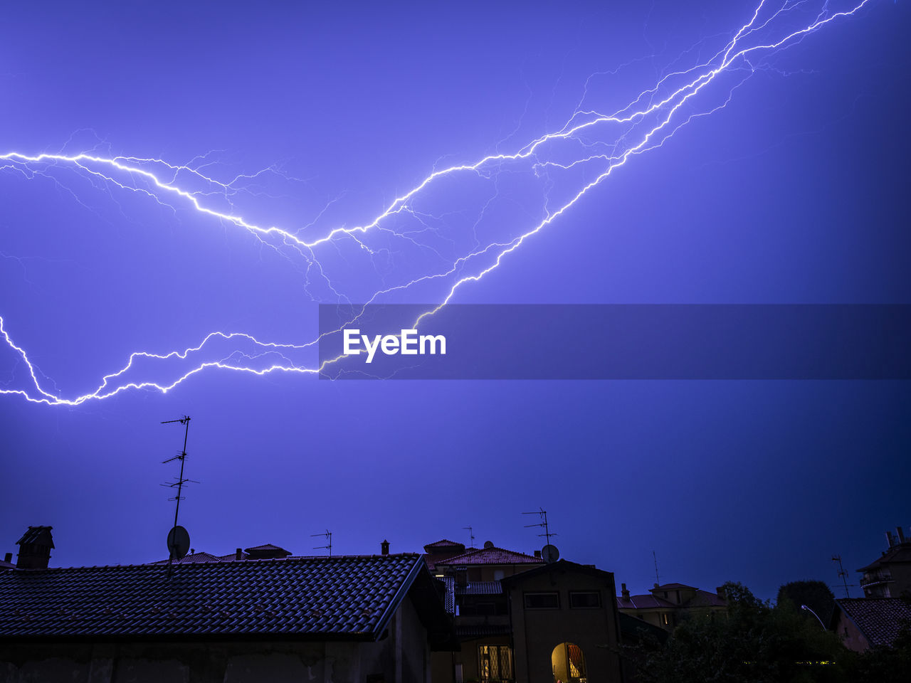 lightning, building exterior, sky, storm, architecture, cloud - sky, built structure, power in nature, thunderstorm, communication, building, power, blue, nature, forked lightning, beauty in nature, night, no people, low angle view, electricity, outdoors, purple