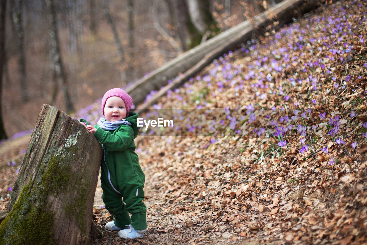 Cute toddler baby in spring forest full of wild irises. spring blossom in the forest. harmony, hope