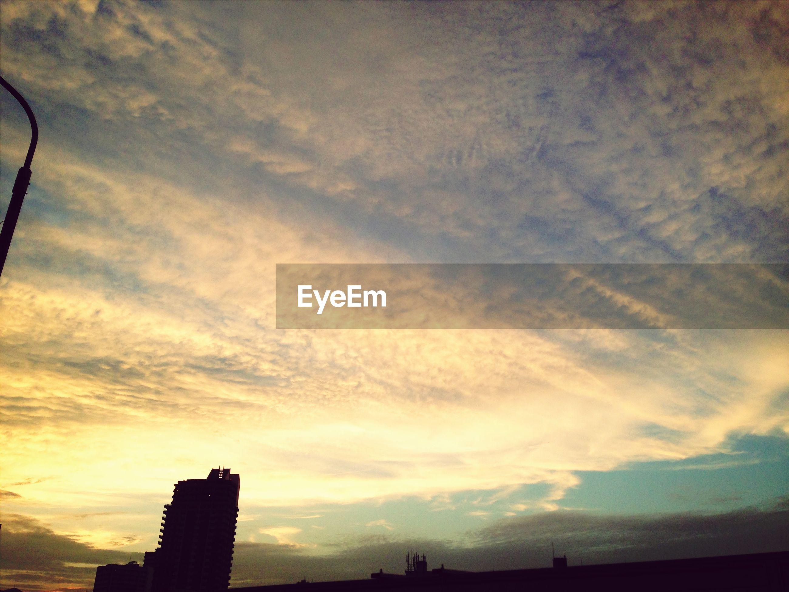 silhouette, sunset, sky, building exterior, built structure, architecture, low angle view, cloud - sky, city, cloud, cloudy, nature, building, beauty in nature, outdoors, outline, no people, orange color, scenics, dusk