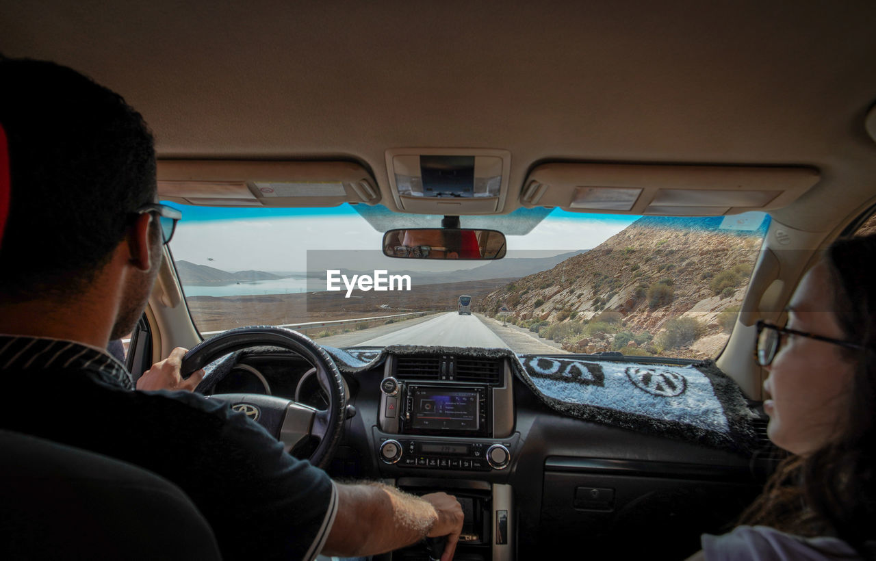 vehicle interior, mode of transportation, transportation, real people, rear view, travel, men, car, windshield, glass - material, lifestyles, control, driving, people, leisure activity, adult, airplane, air vehicle, two people, outdoors, mature men