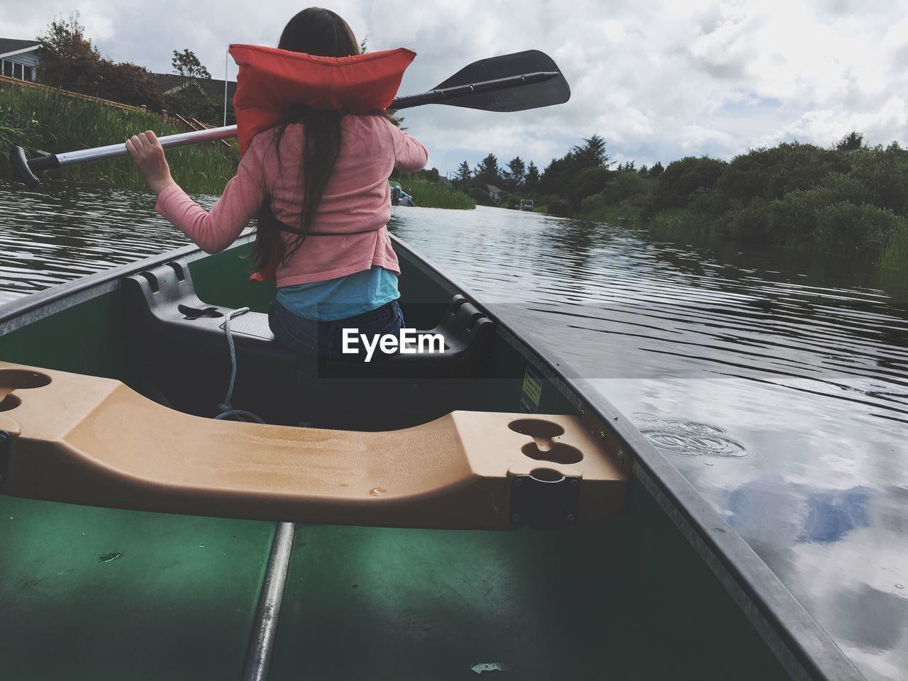 Rear View Of Woman Canoeing In River Against Cloudy Sky
