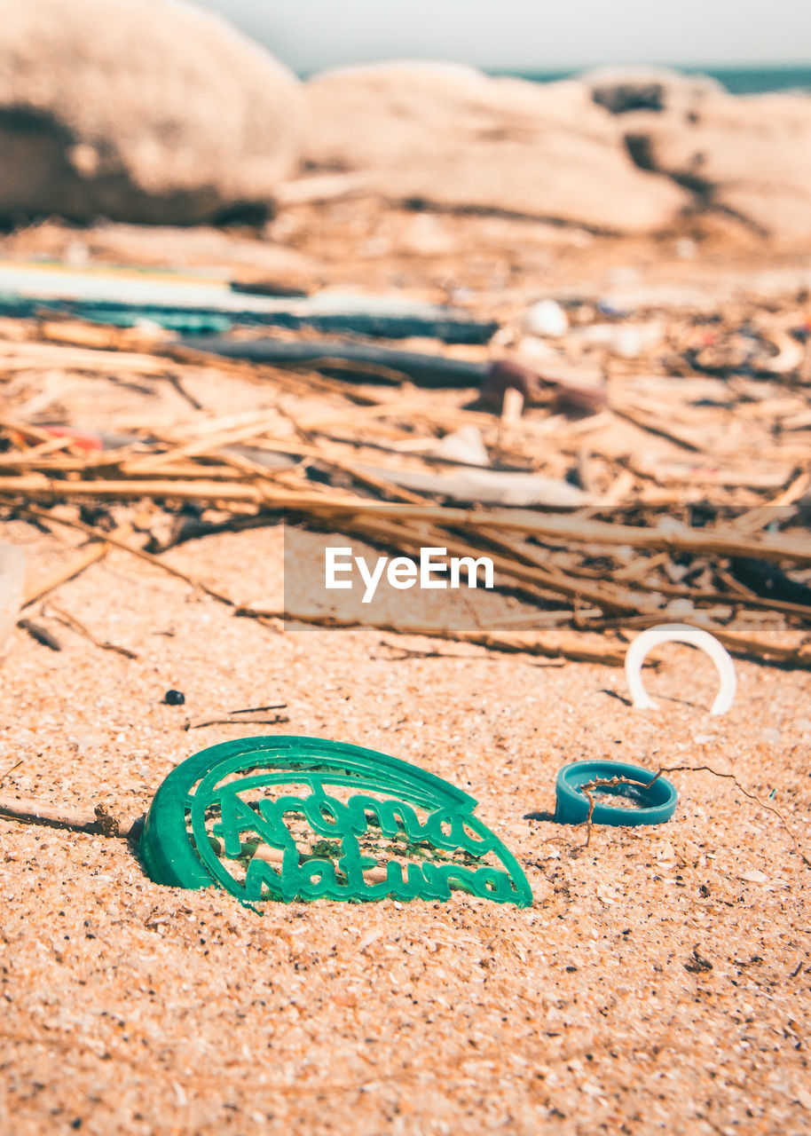 land, text, sand, nature, close-up, communication, no people, western script, day, beach, focus on foreground, outdoors, sunlight, selective focus, green color, brown, number, rock, finance, art and craft, message