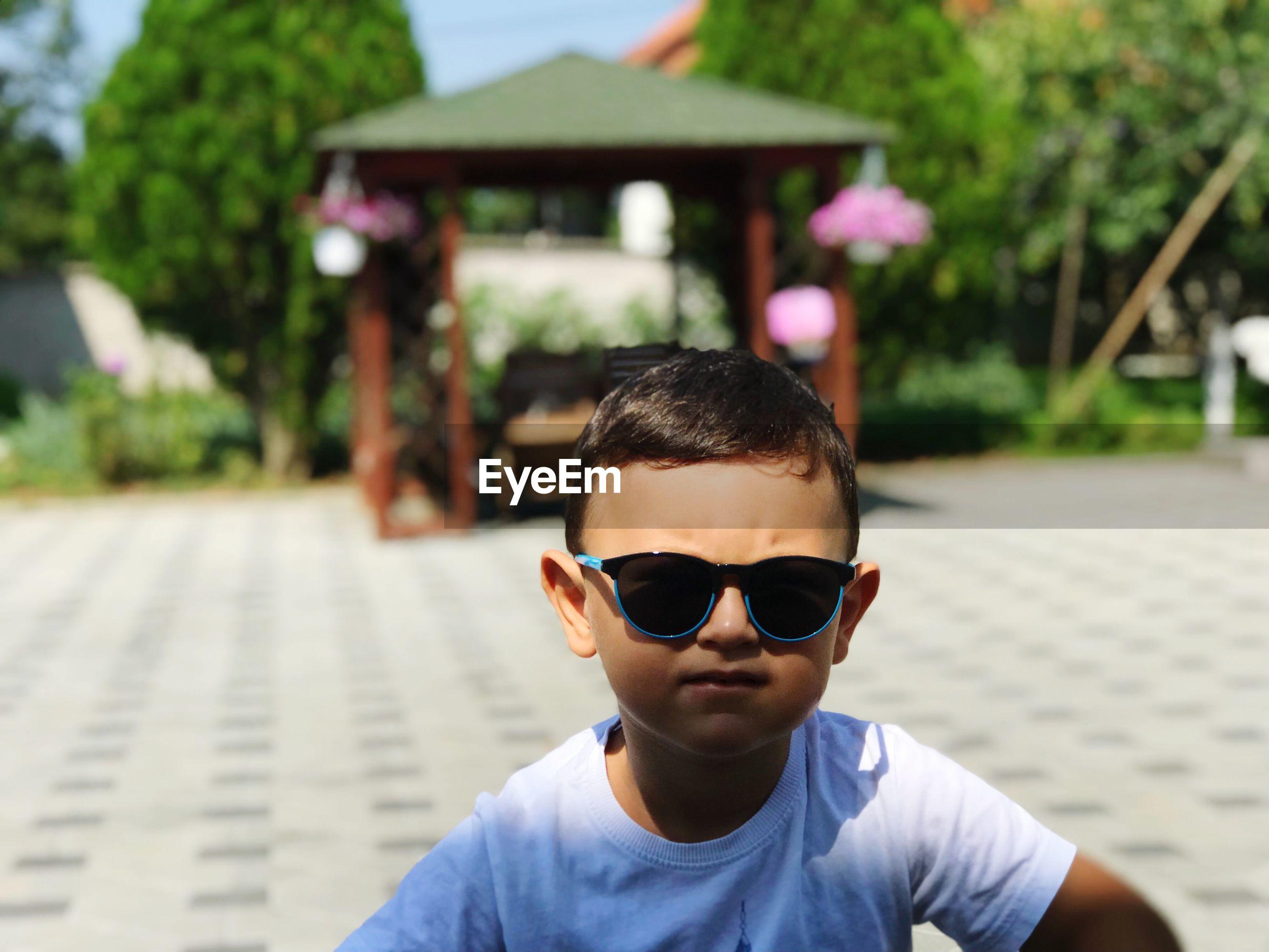 Portrait of cute boy wearing sunglasses in city