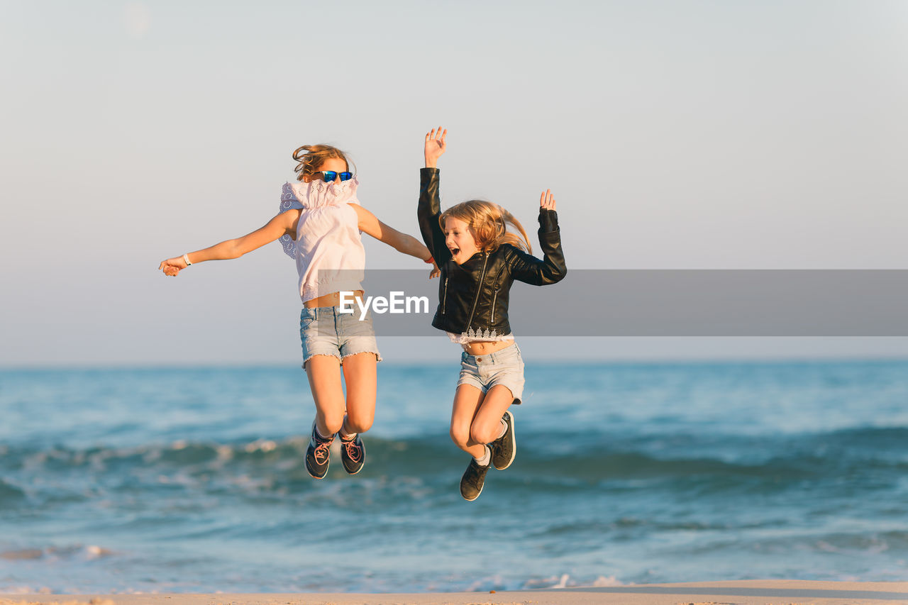 Full Length Of Happy Carefree Girls Jumping At Beach Against Sky During Sunset