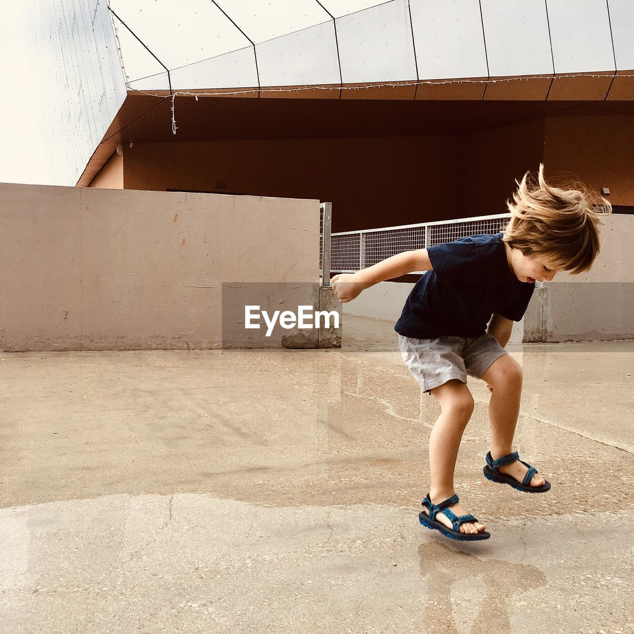 Full length of boy jumping on puddle