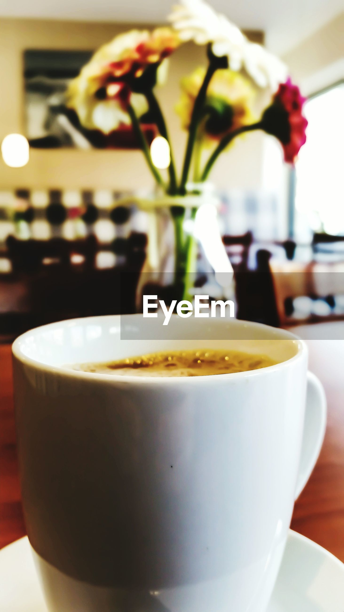 Close-up of coffee cup with blurred vase