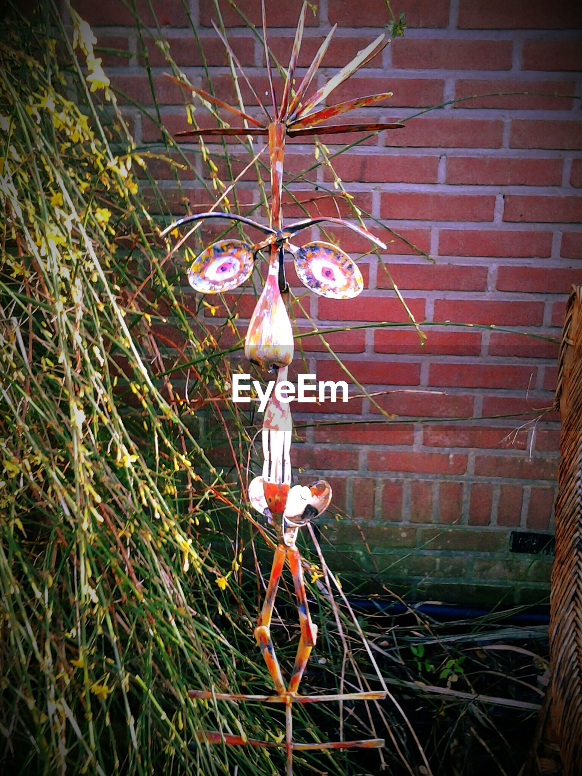 Human face made by metal structure hanging on twigs at yard