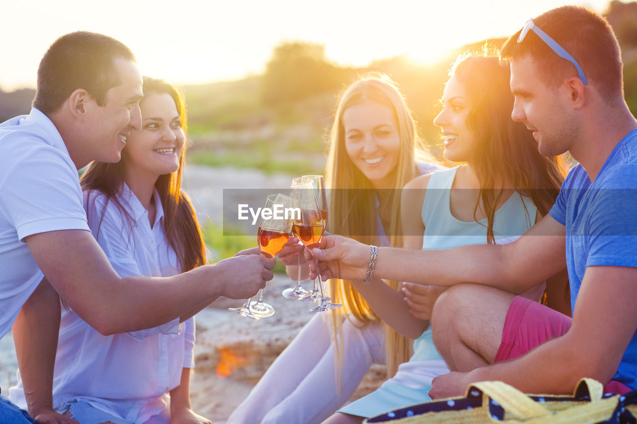 Group of people drinking wine during sunset