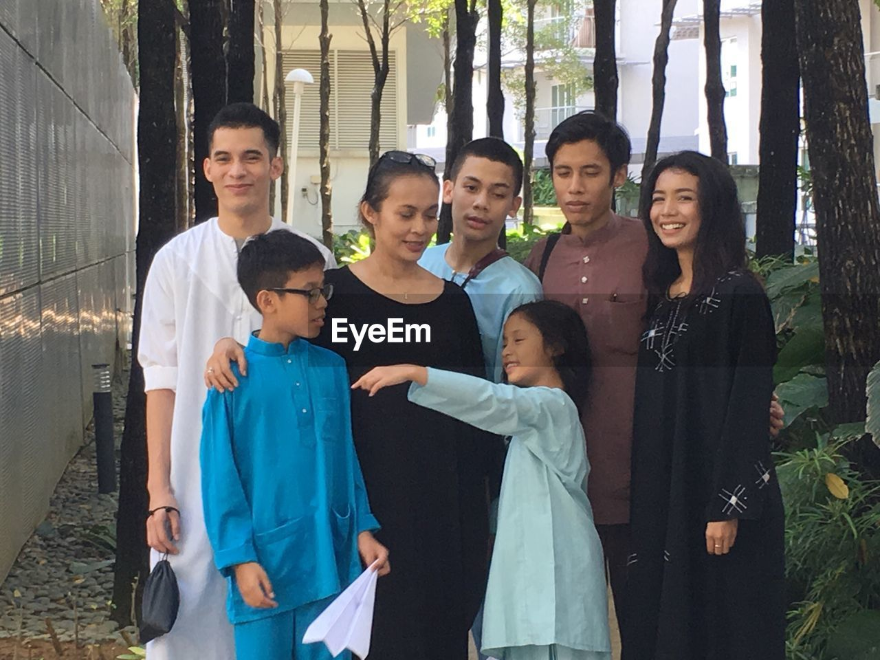 smiling, boys, looking at camera, portrait, happiness, family, standing, lifestyles, togetherness, teenager, love, son, girls, outdoors, bonding, young adult, real people, young women, cheerful, day, women, group of people, tree, men, friendship, people
