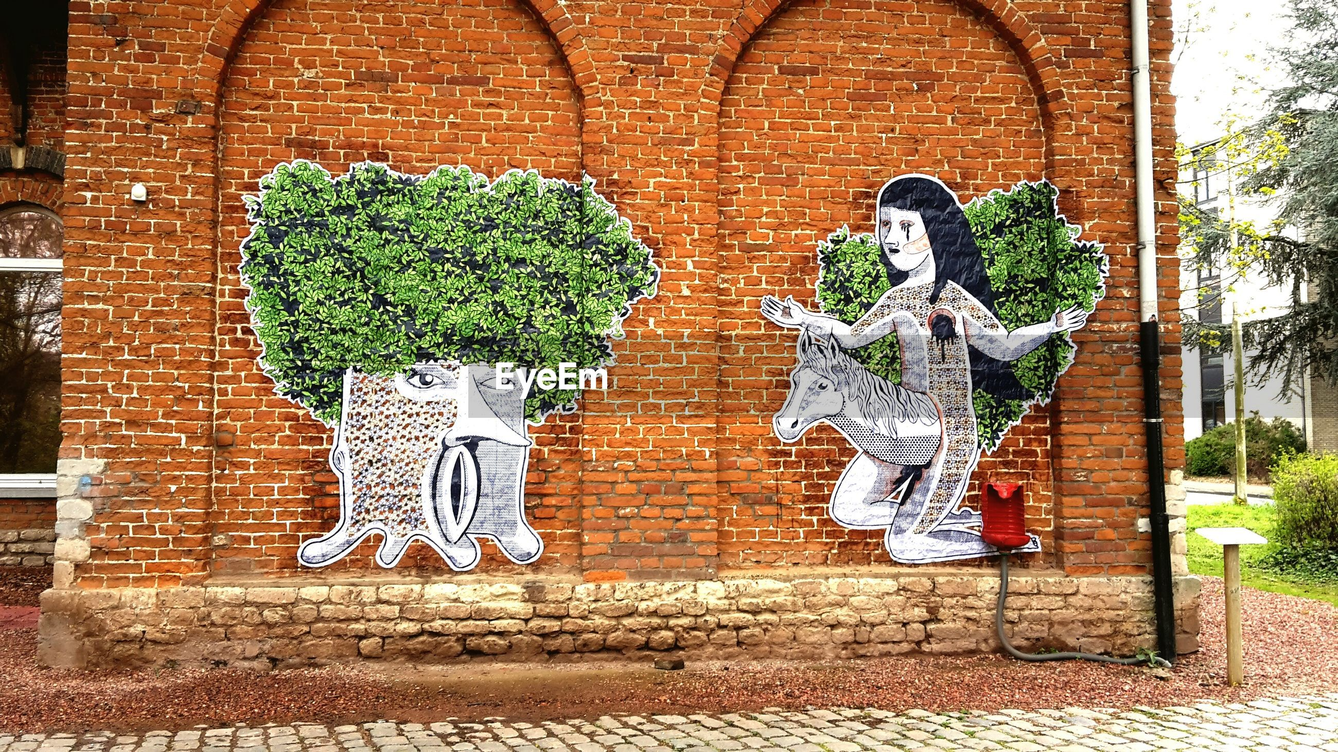 art, art and craft, creativity, wall - building feature, built structure, green color, human representation, plant, wall, brick wall, architecture, growth, graffiti, leaf, building exterior, no people, animal representation, design, day