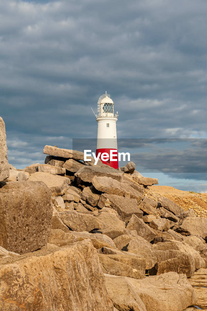 LIGHTHOUSE BY ROCK ON SEA AGAINST SKY