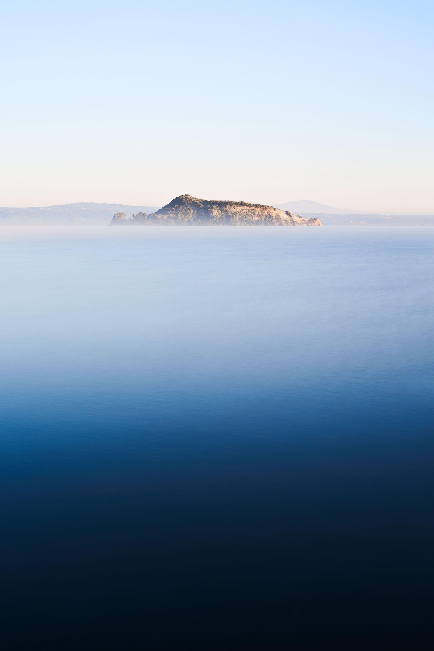 Martana island, an isolated solitary island in the bolsena lake, long exposure water and fog