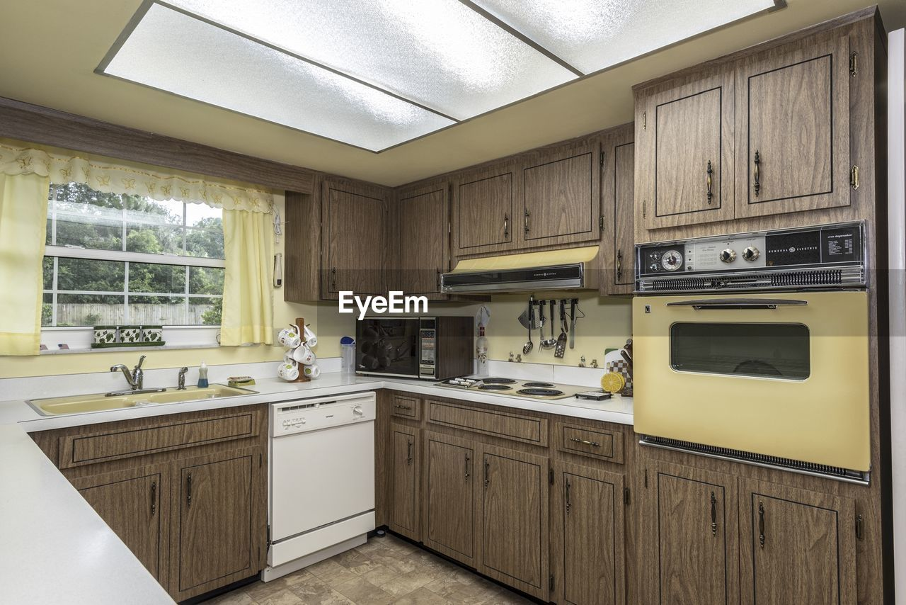 kitchen, indoors, domestic kitchen, domestic room, cabinet, appliance, home, household equipment, no people, oven, stove, kitchen counter, home interior, furniture, architecture, absence, sink, window, microwave, modern, luxury, clean