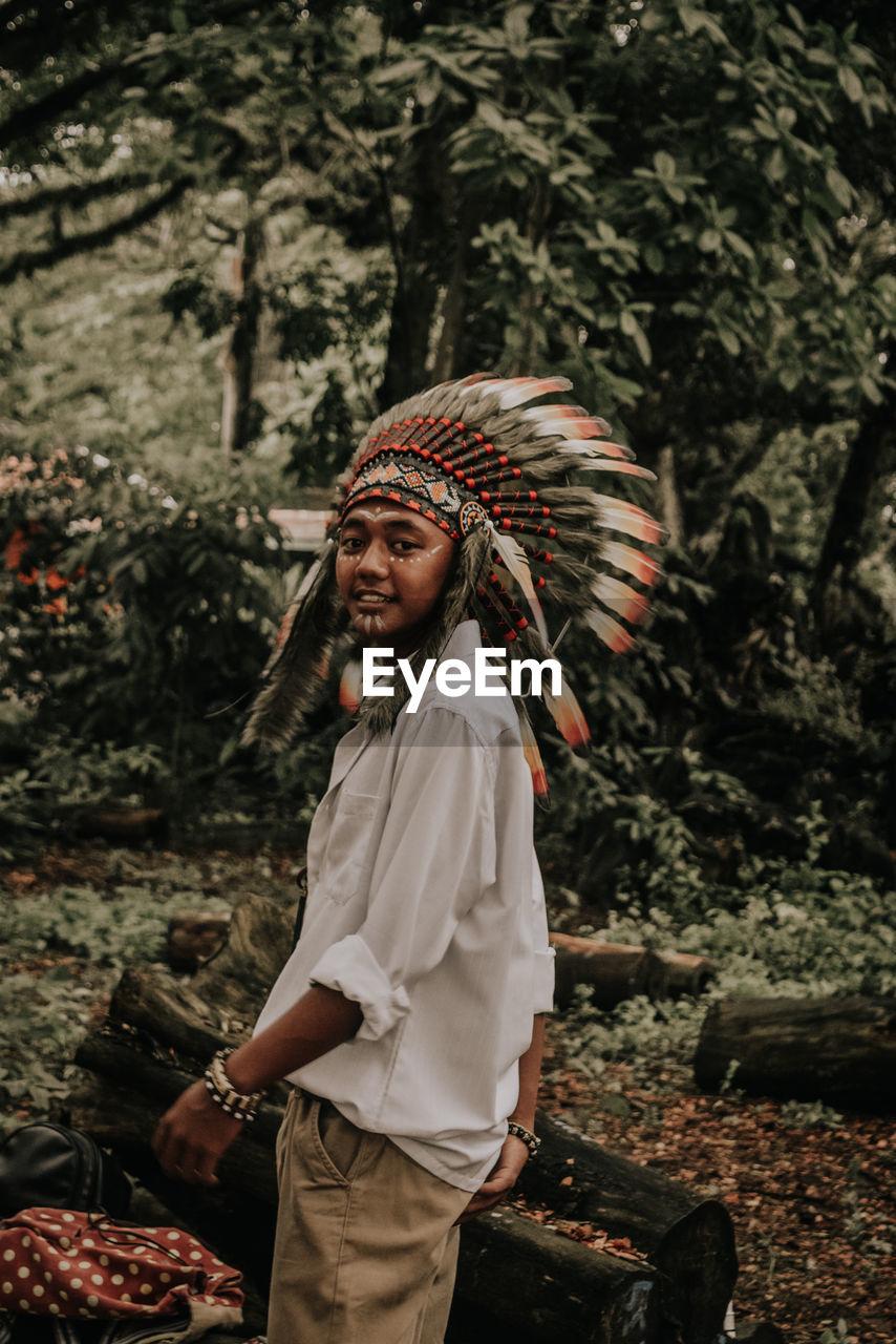 Portrait of smiling man wearing headdress in forest