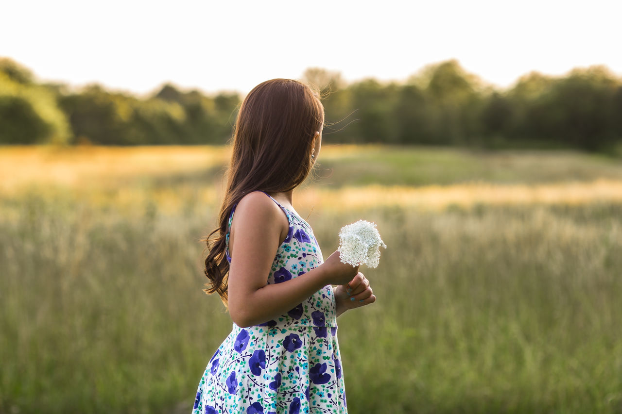 Girl Holding Flower While Standing On Field Against Sky
