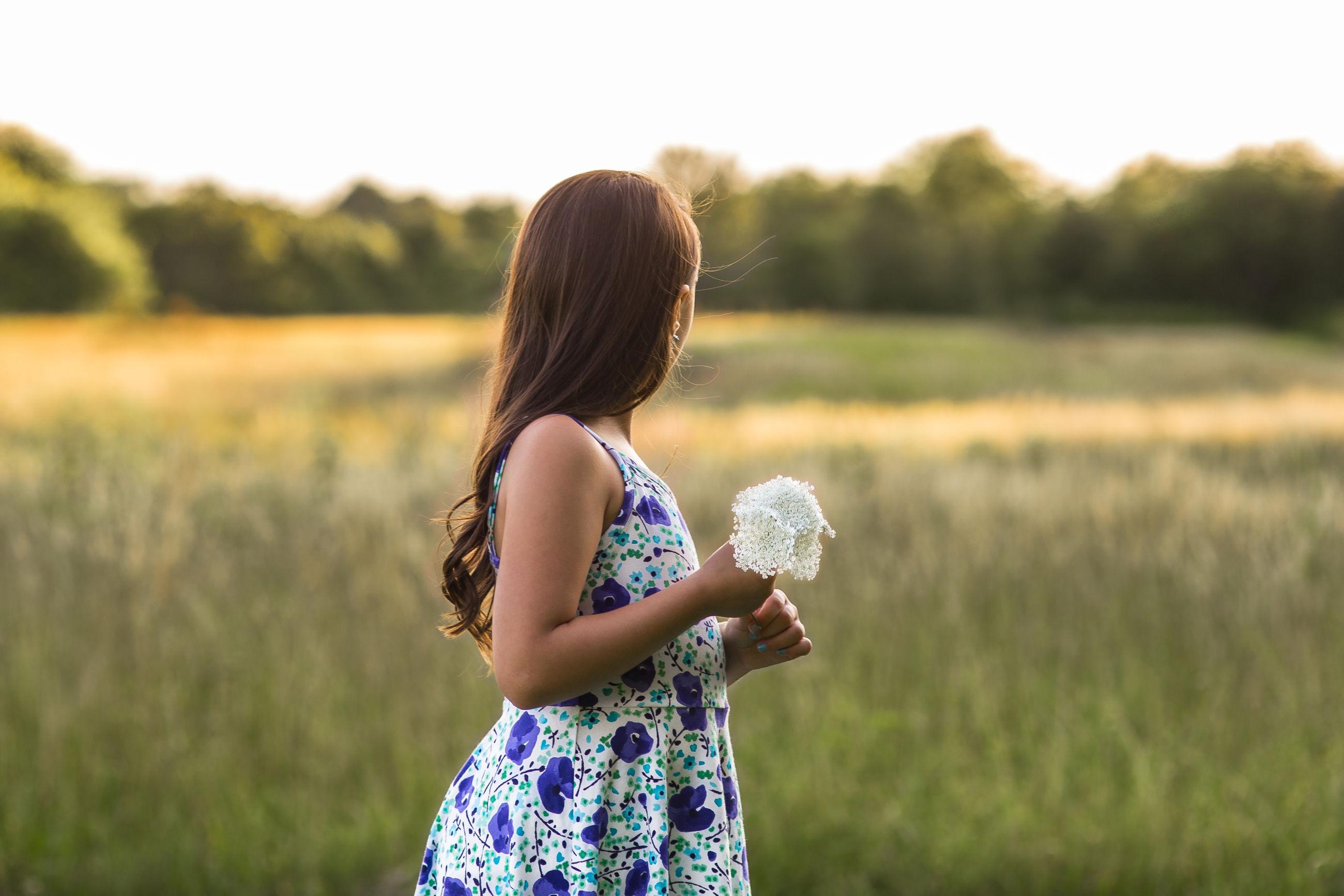 Girl holding flower while standing on field against sky