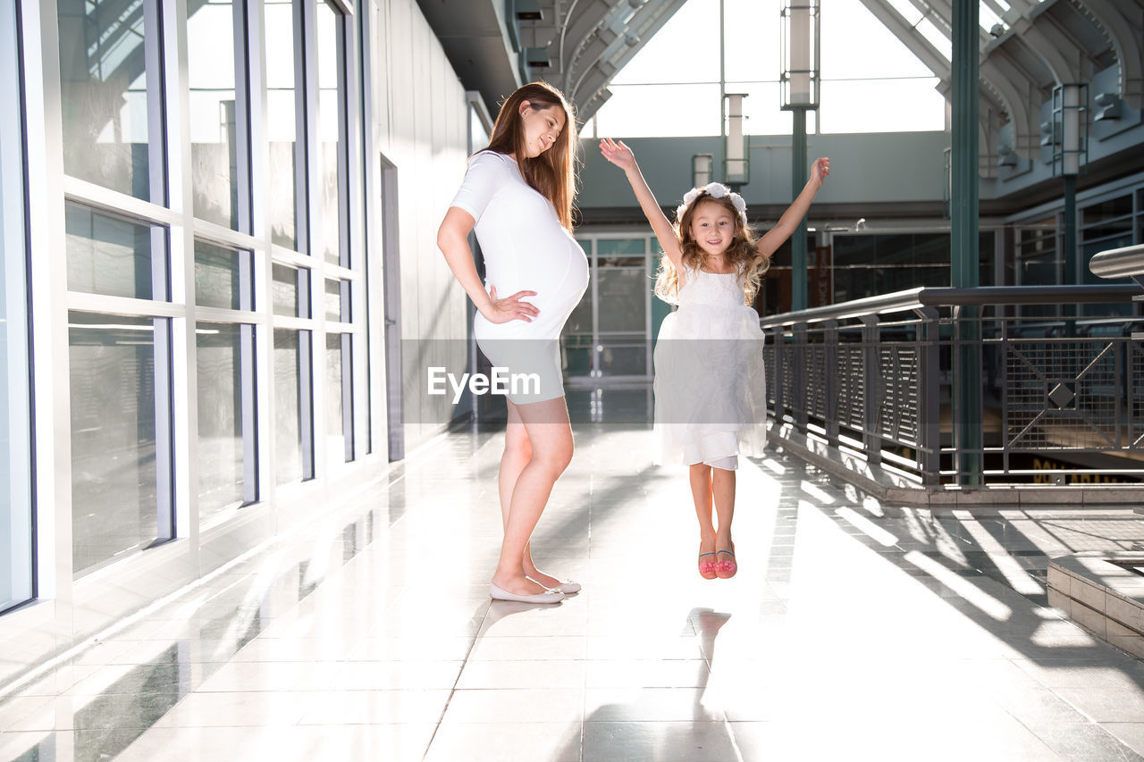 Portrait Of Happy Daughter Jumping By Pregnant Mother At Corridor