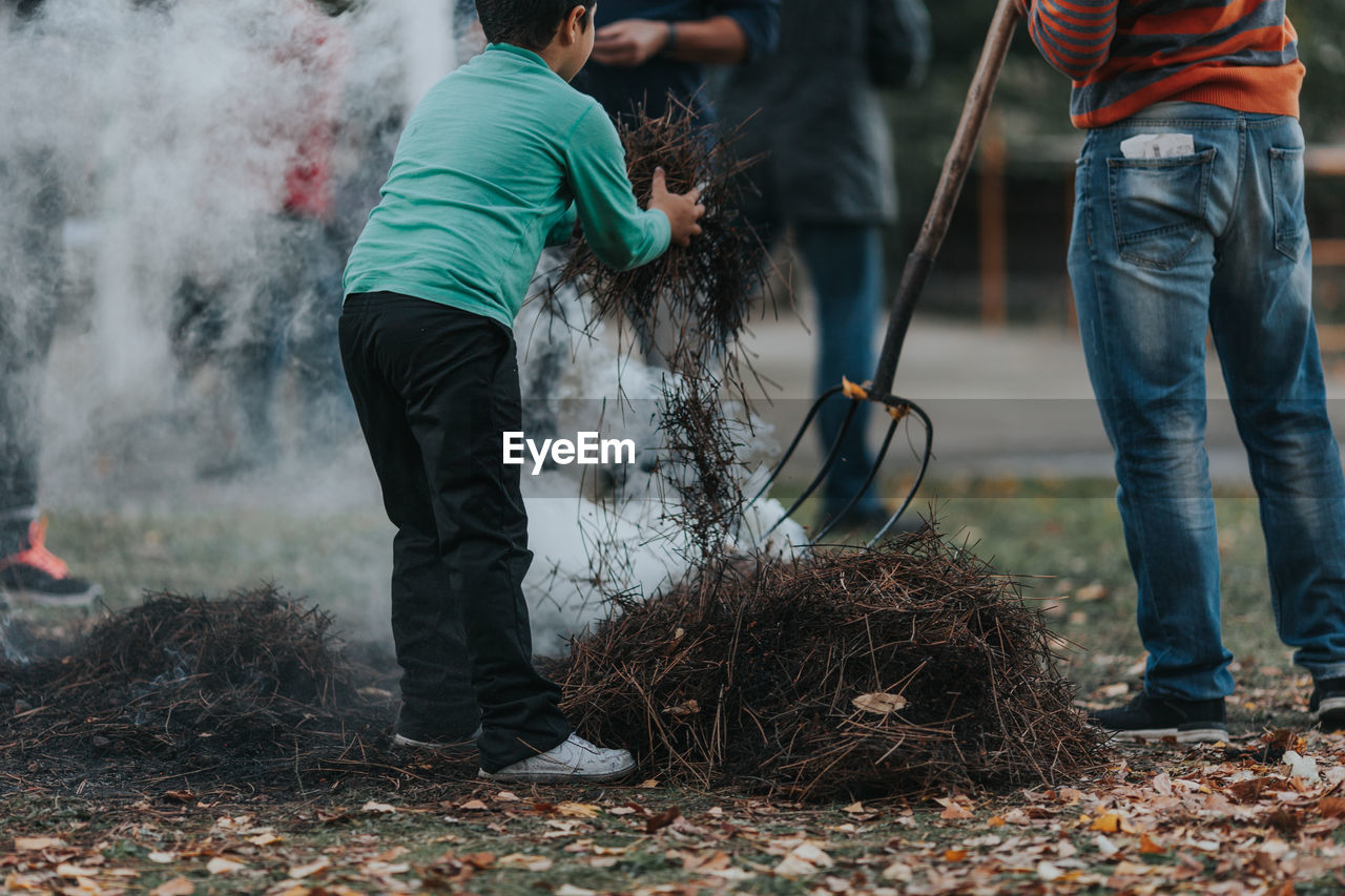 People burning dried twigs on field
