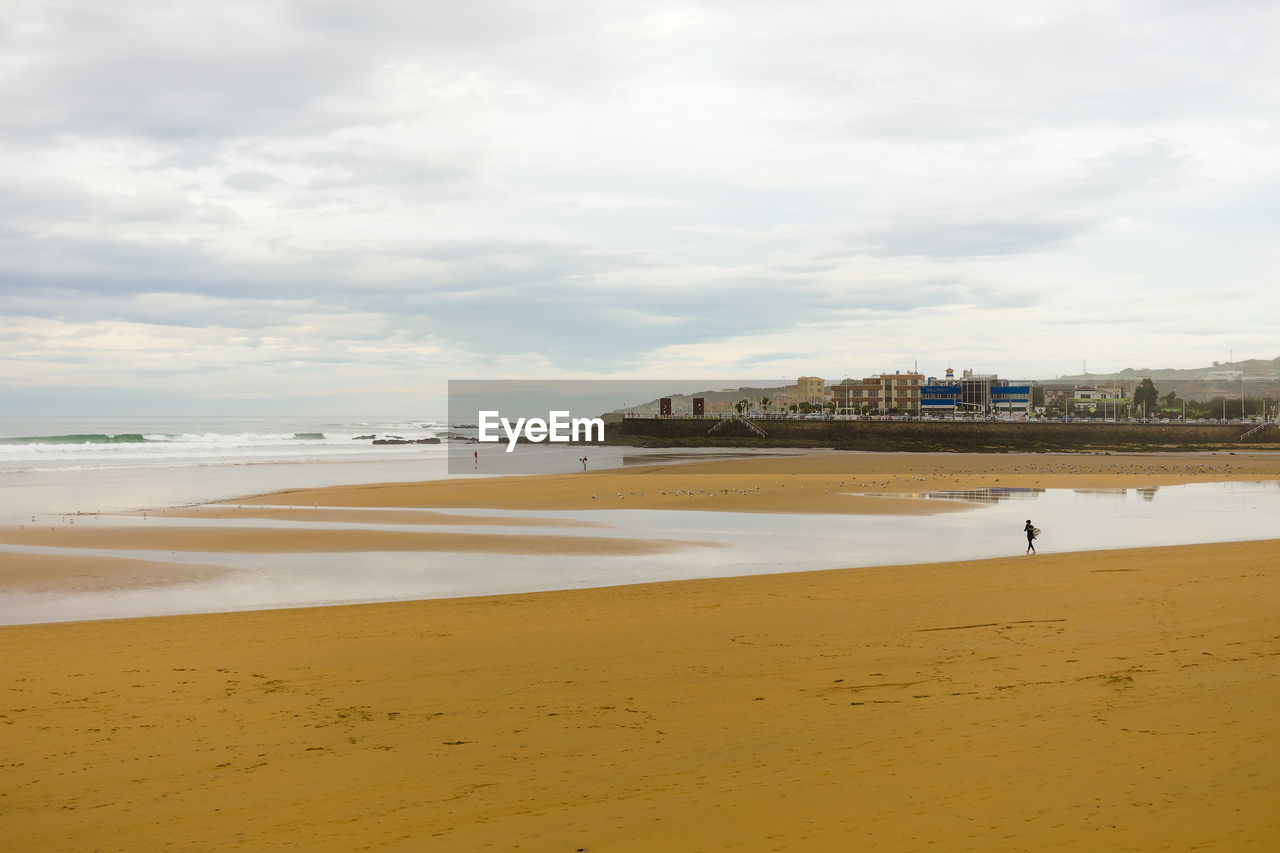 water, beach, land, sky, cloud - sky, sand, sea, nature, beauty in nature, built structure, architecture, scenics - nature, day, tranquil scene, incidental people, building exterior, outdoors, tranquility
