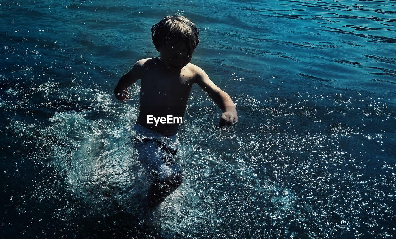 Shirtless boy wading in sea