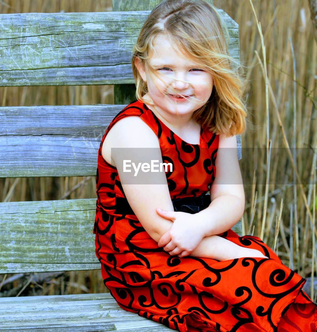 child, childhood, one person, real people, girls, females, smiling, women, blond hair, lifestyles, three quarter length, leisure activity, day, casual clothing, innocence, sitting, emotion, front view, hair, outdoors, hairstyle