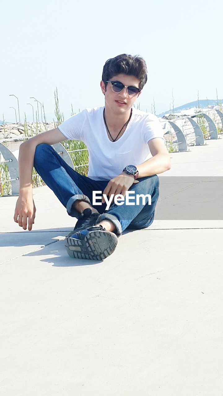 sitting, casual clothing, sunglasses, full length, young adult, leisure activity, one person, day, young men, outdoors, lifestyles, real people, wireless technology, sky, people