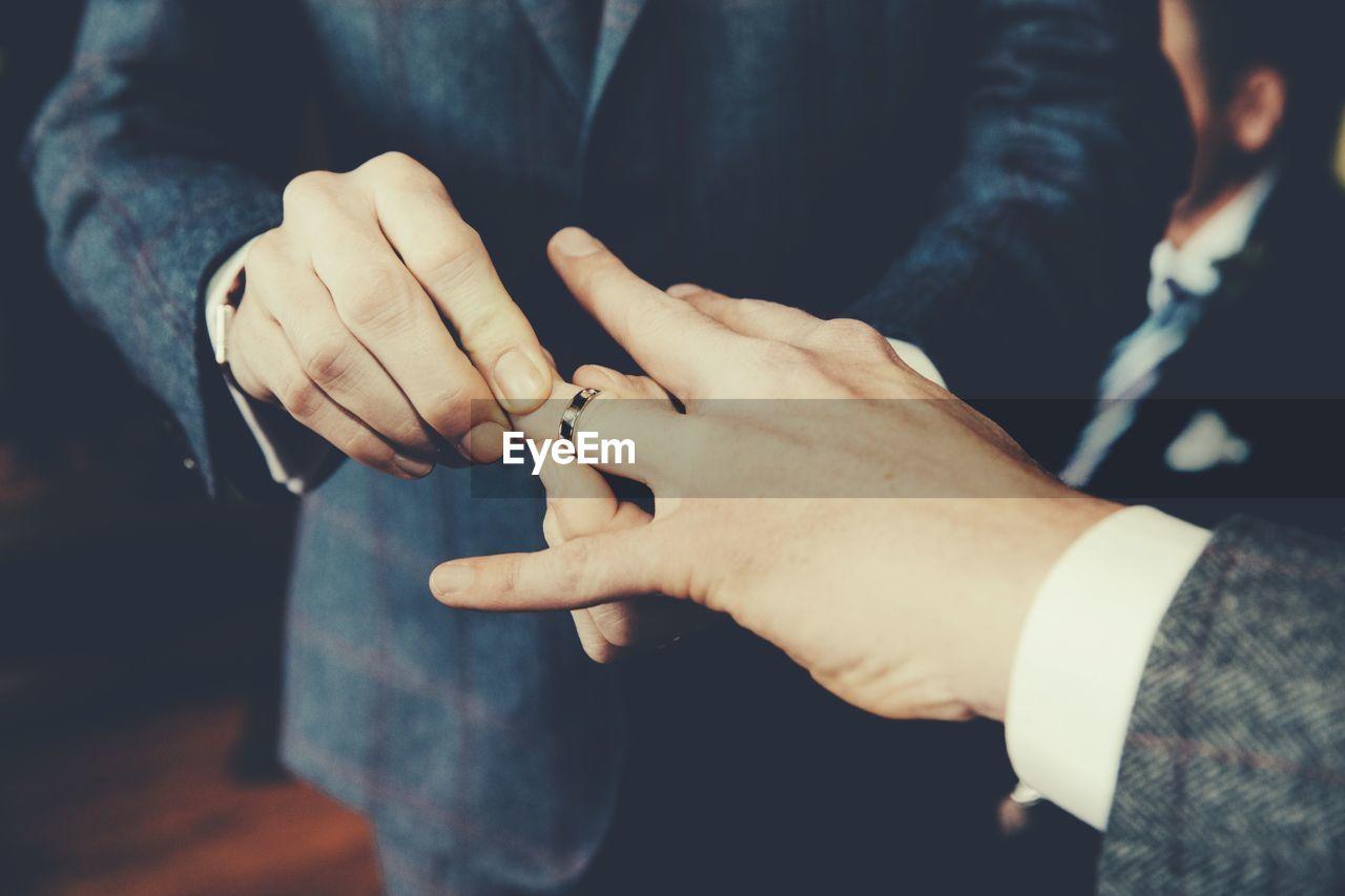 Gay Men Exchanging Rings At Wedding Ceremony