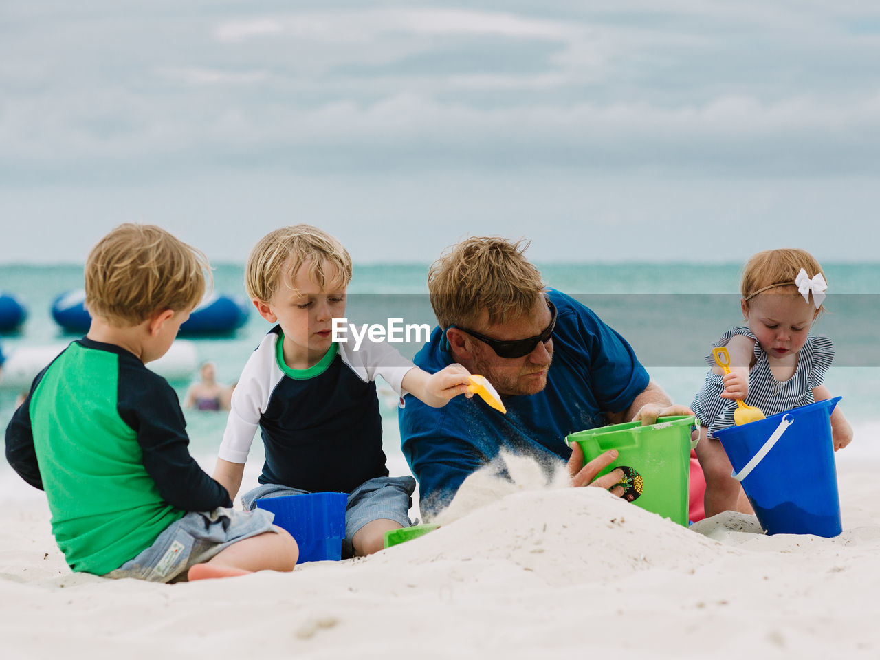 Family Making Sand Castle At Beach