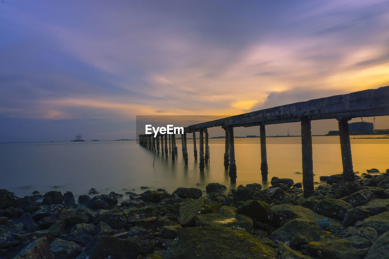 sky, sunset, water, sea, cloud - sky, rock, solid, rock - object, beauty in nature, scenics - nature, built structure, nature, architecture, orange color, bridge, connection, bridge - man made structure, beach, tranquil scene, no people, horizon over water, outdoors, architectural column, groyne