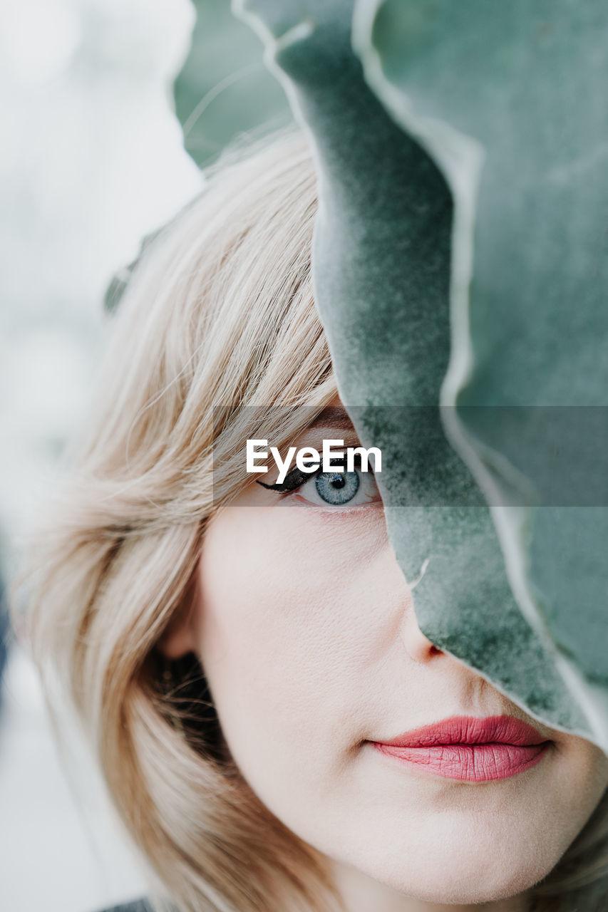 Close-Up Portrait Of Woman By Leaf