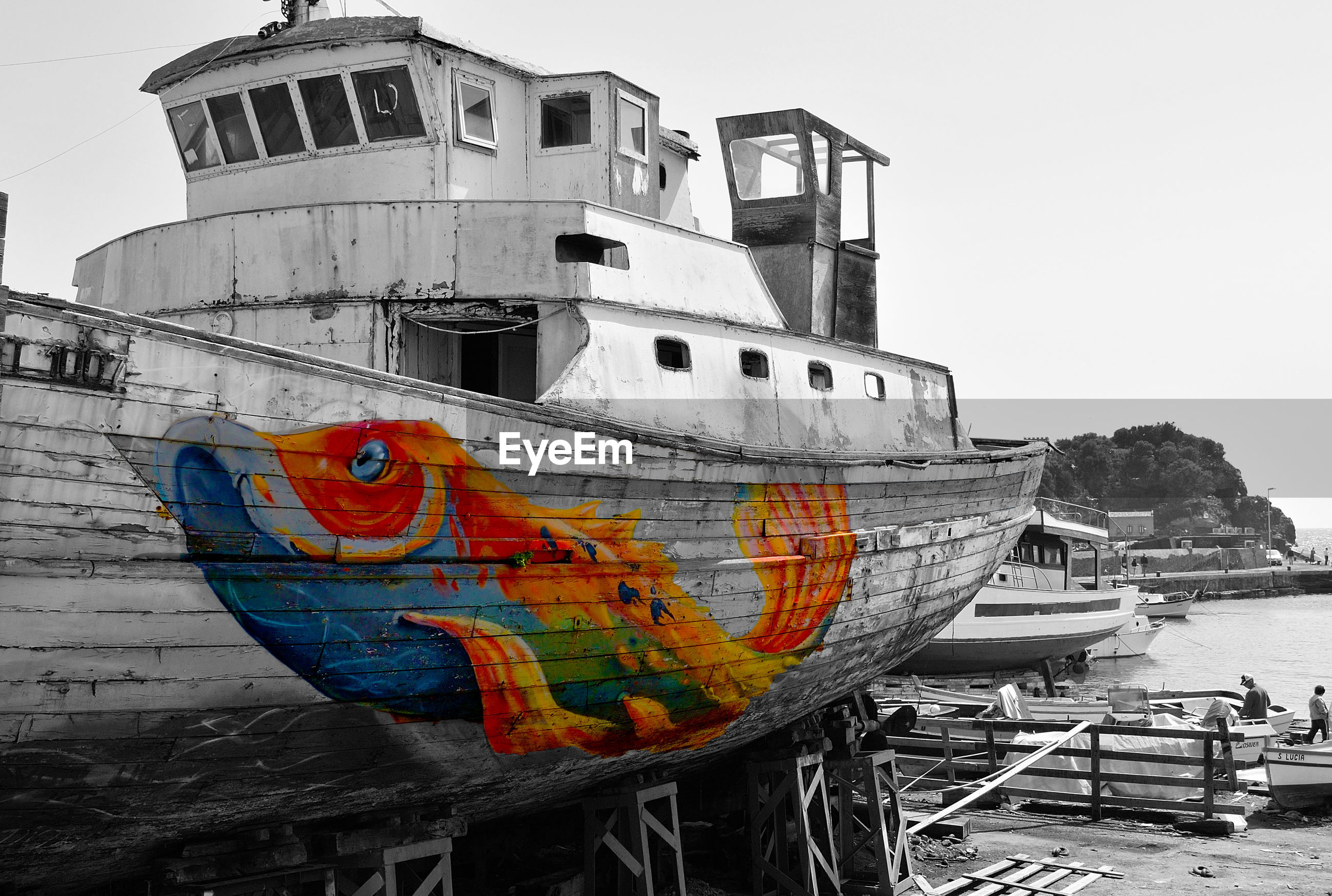 Colorful painting of fish on boat moored at harbor