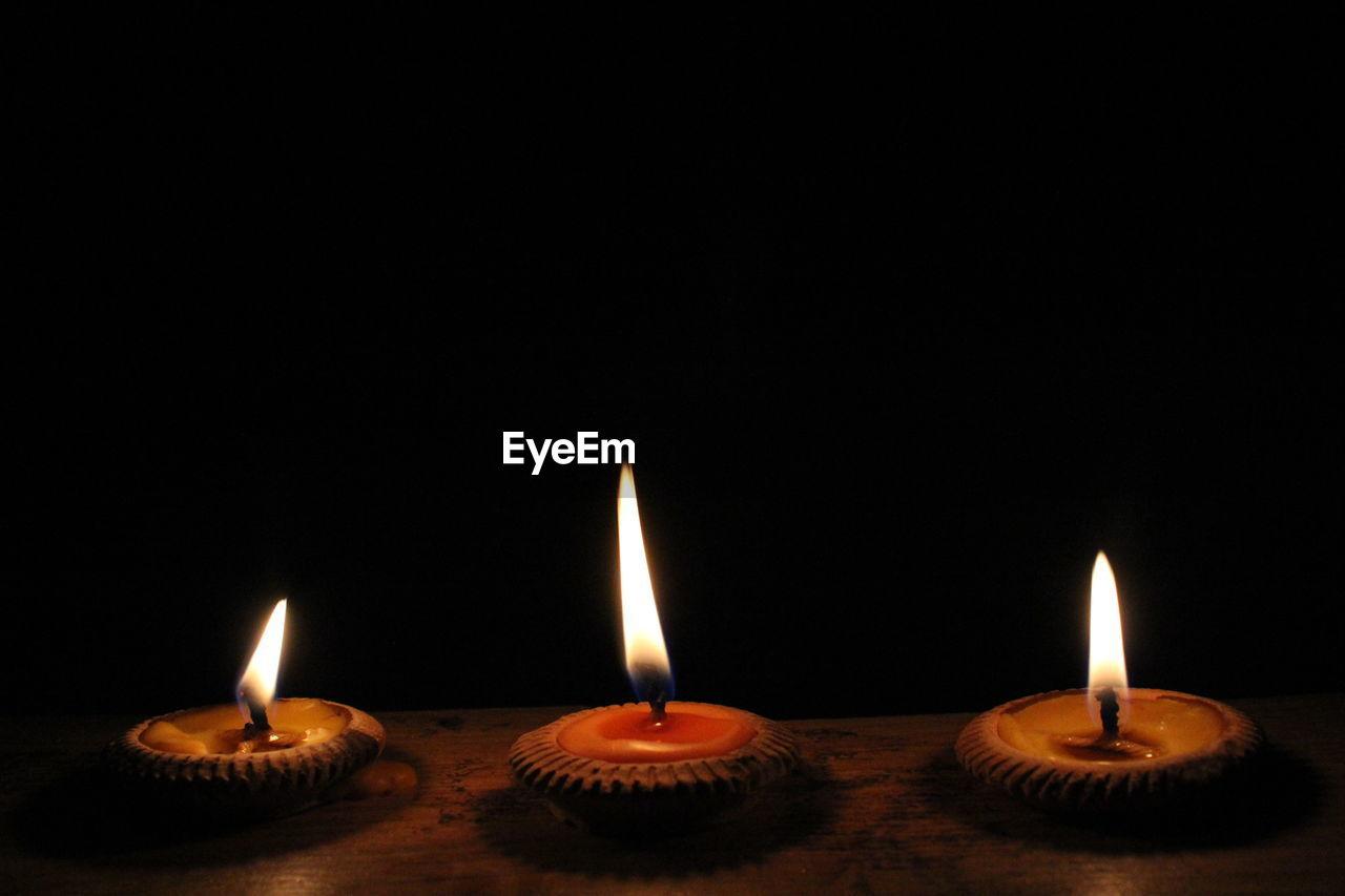 Close-up of lit diyas against black background