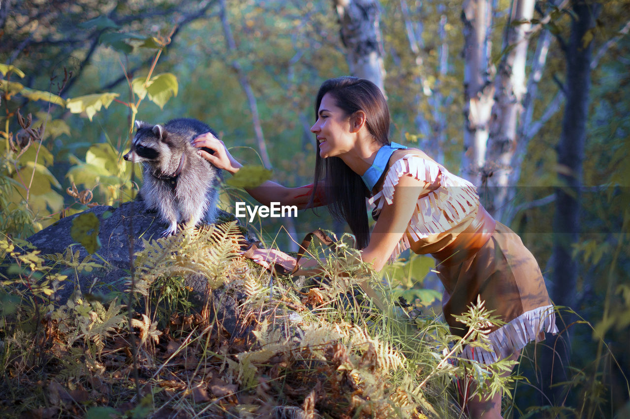 Side View Of Young Woman In Traditional Clothing Stroking Raccoon In Forest
