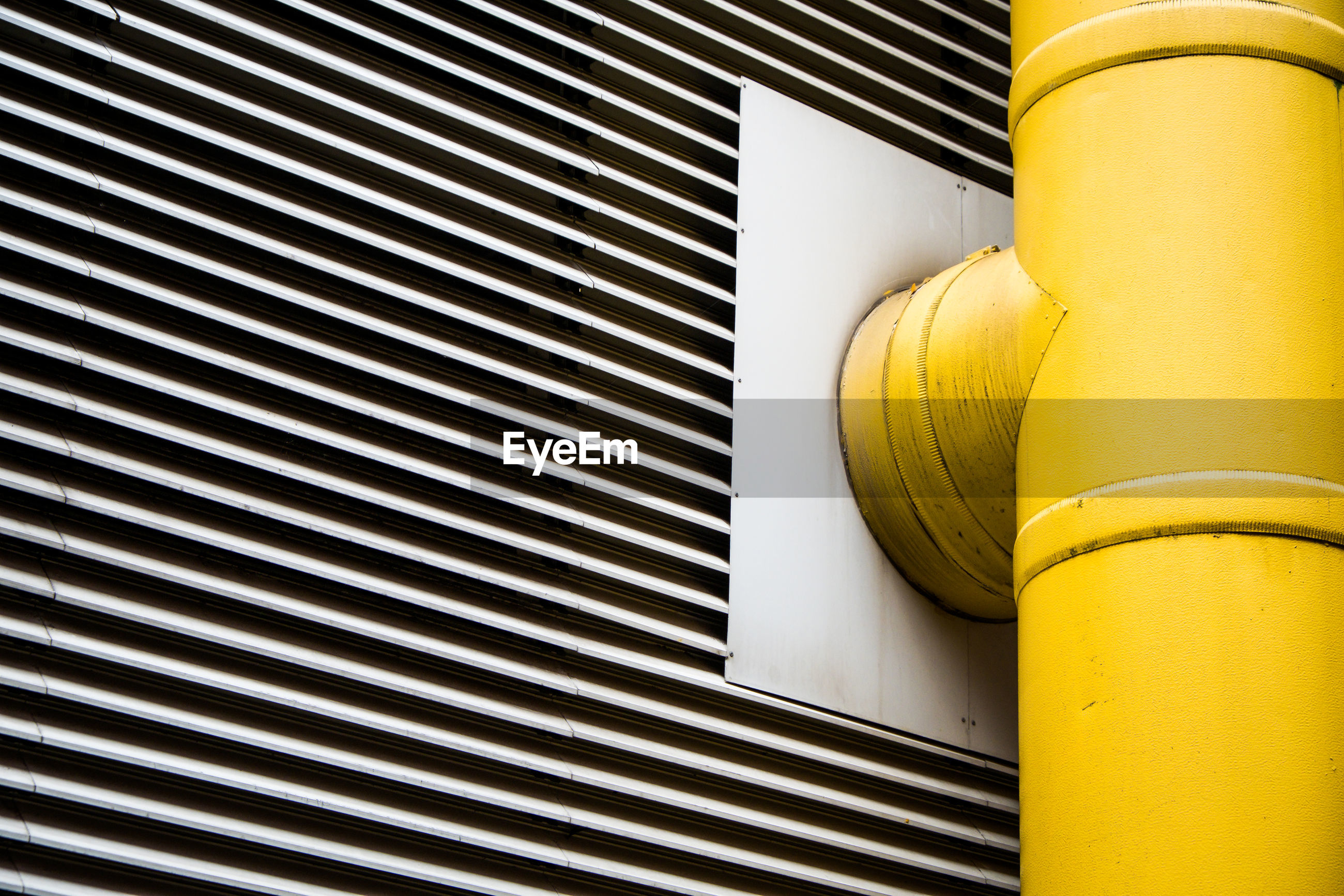 Low angle view of yellow pipe against wall