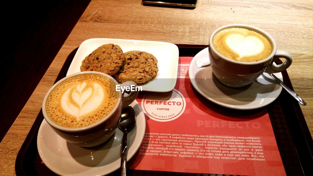 coffee cup, coffee - drink, drink, refreshment, saucer, food and drink, frothy drink, cappuccino, table, indoors, froth art, latte, no people, high angle view, cafe, freshness, beverage, close-up, day