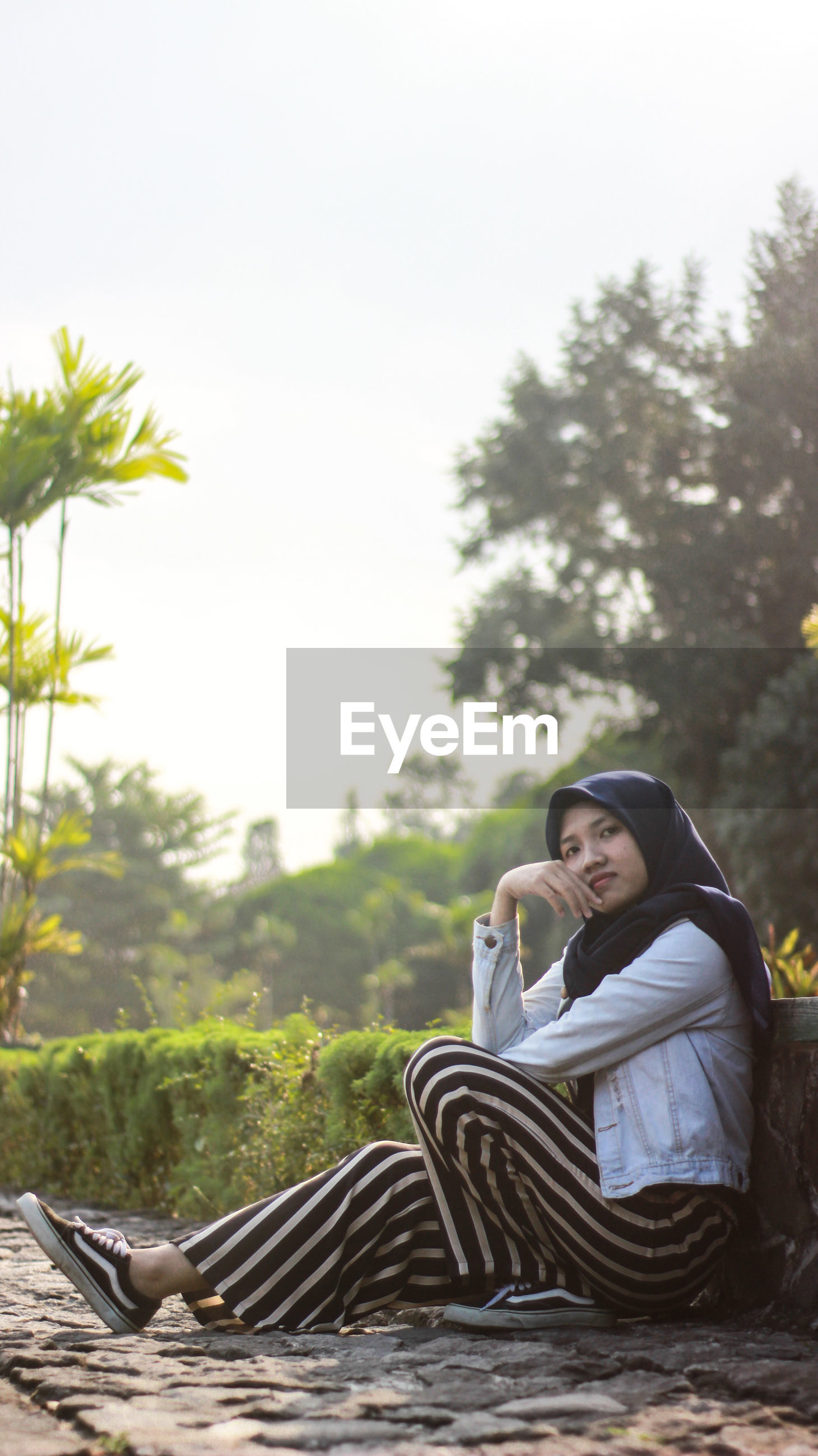 SMILING YOUNG WOMAN SITTING ON PLANT AGAINST TREES